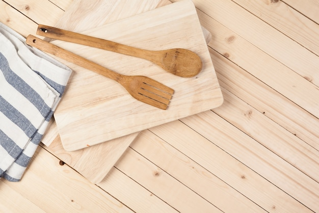 Wooden spoons and other cooking tools with blue napkins on the kitchen table.