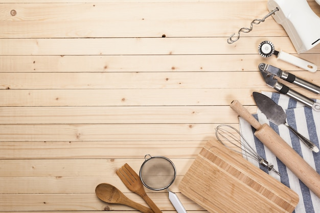 Wooden spoons and other cooking tools with blue napkins on the kitchen table