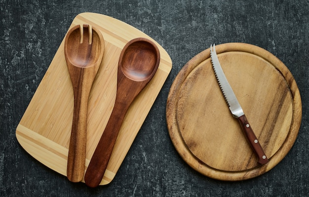 Wooden spoons and tomato knife on cutting boards, top view