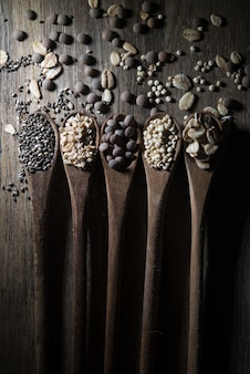 Wooden spoons with cereals and seeds on wood