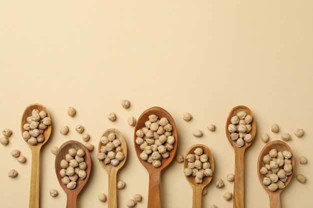 Wooden spoons with chickpea on beige