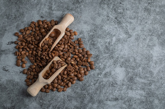 Wooden spoons with coffee beans on a gray background.