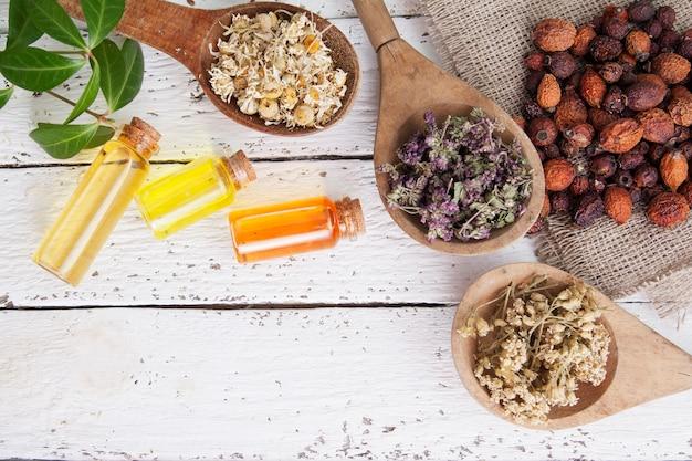 Деревянные ложки с сушеными лекарственными травами, шиповником и бутылками с эссенцией. лекарственные чаи и настойки как альтернативная медицина