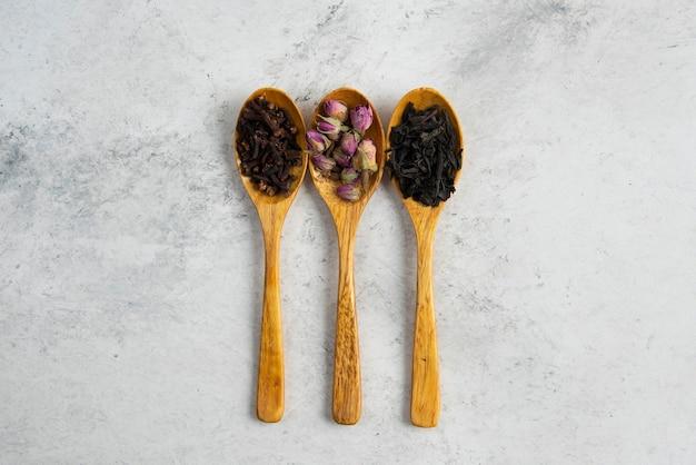 Cucchiai di legno con rose essiccate, tè sfusi e chiodi di garofano.