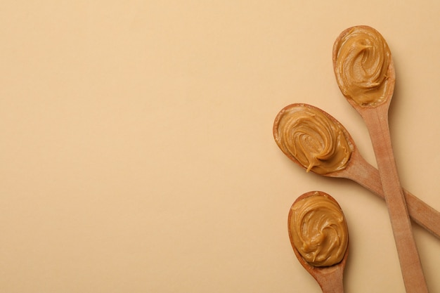 Wooden spoons with peanut butter on beige background