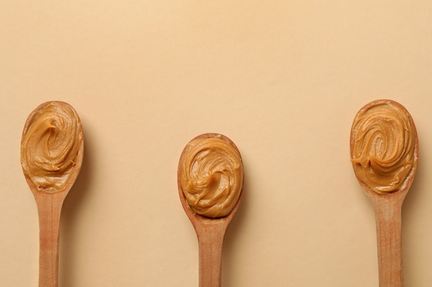 Wooden spoons with peanut butter isolated Premium Photo