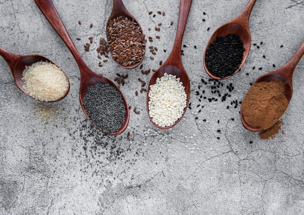 Wooden spoons with various healthy seeds and spices on gray concrete desk