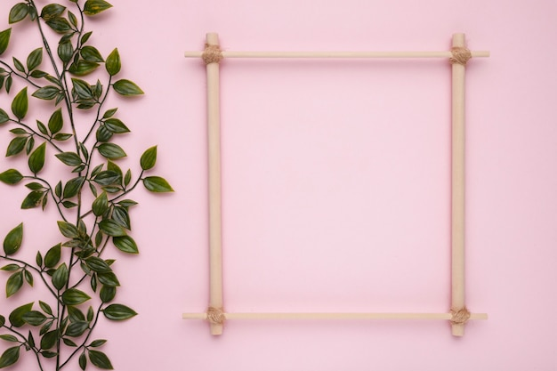 Wooden square frame with artificial green leaves on pink backdrop