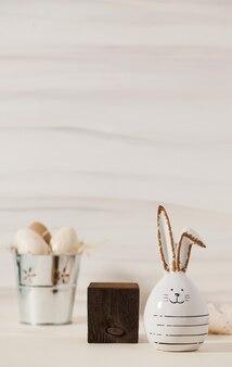 Деревянный квадратный подиум белый керамический кролик и пасхальные яйца в металлическом горшке счастливой пасхи композиции