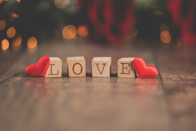 배경에 보케 조명으로 [love]라고 적힌 나무 사각형