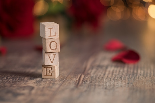 Wooden squares with [love] written on them with bokeh lights on the backgrounds