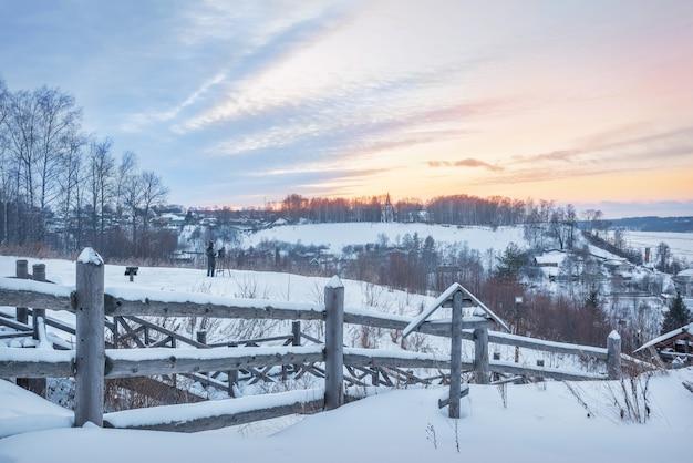 Деревянная лестница и памятник художнику левитану на горе левитан в плёсе в снегу в свете заходящего зимнего солнца