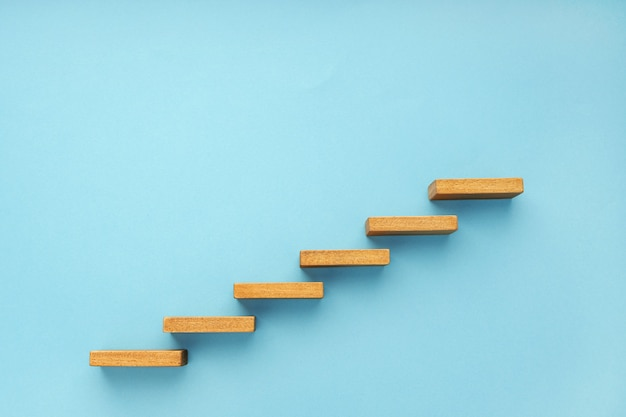 Wooden staircase on blue background growth increasing business concept copy space