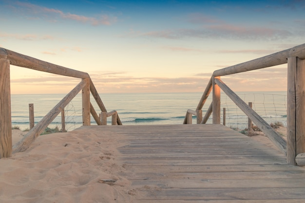 Wooden staircase and railing access to the beach sand at sunset