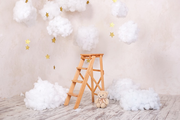 Wooden staircase stool with clouds in the children room. scandinavian style. rustic room interior. christmas holiday decorations.