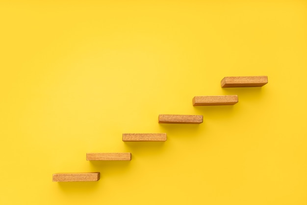 Wooden staircase on yellow background growth increasing business concept copy space