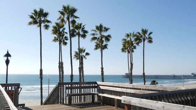 Wooden stairs, beach access in california usa. coastal stairway, pacific ocean waves and palm trees.