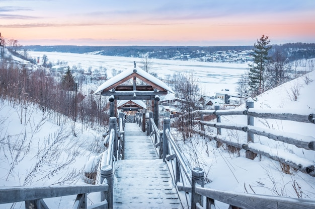 Деревянная лестница с горы левитан и вид на замерзшую волгу в плёсе в снегу в свете заходящего зимнего солнца