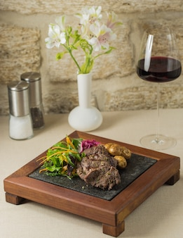 A wooden stand of steak and potatoes with greenery salad