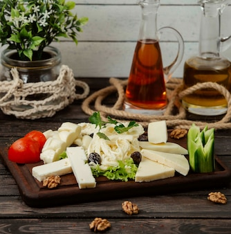 Деревянная подставка с нарезанными сырами разных видов на столе