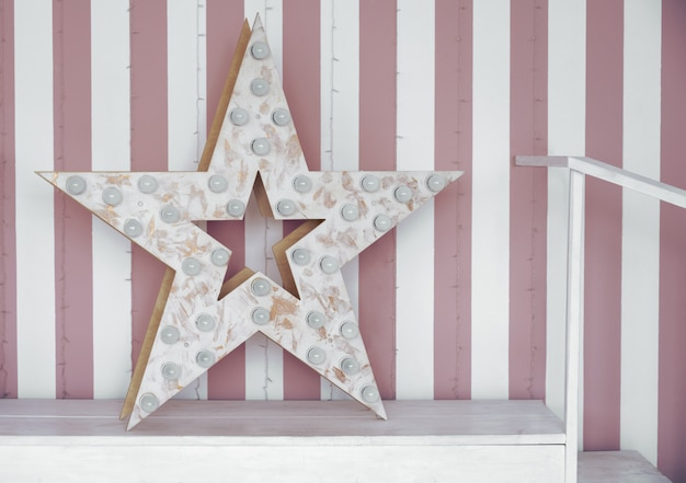 Wooden star with lamps bulbs with strapped pink and white wall