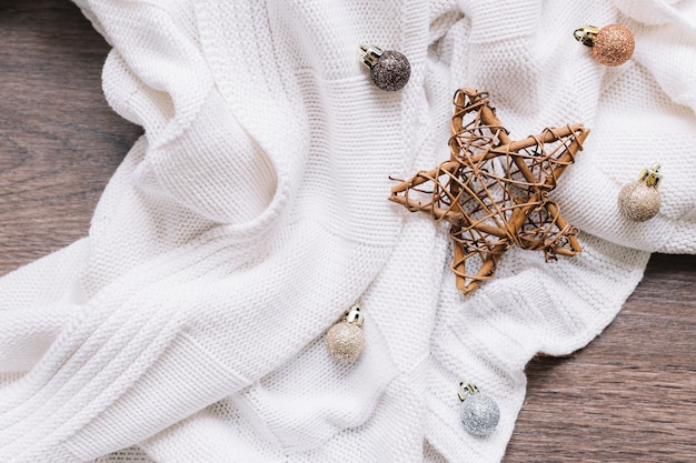 Wooden star with shiny baubles on table