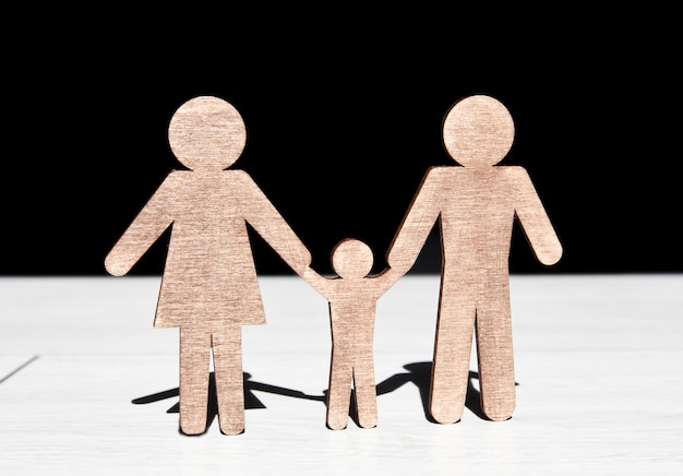Wooden statuettes of mother, father and their child on wooden floor