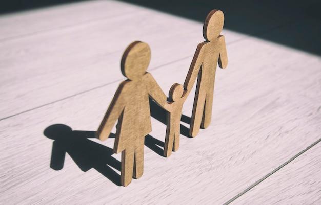 木の床に母、父とその子の木製の小像