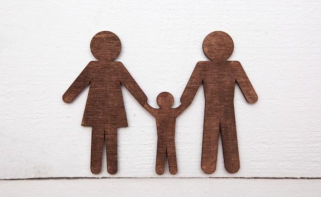 Деревянные статуэтки матери, отца и их ребенка на деревянном полу