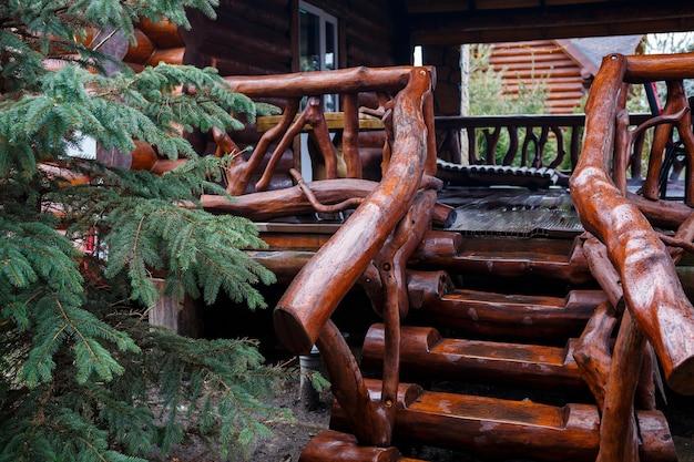 테라스로 가는 나무 계단. 거리에 통나무 집에서 계단