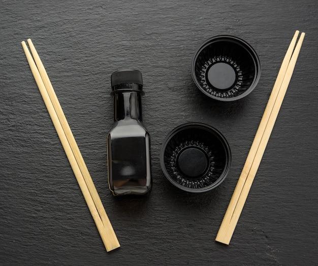 Деревянные палочки для суши, бутылка соевого соуса и одноразовые пластиковые тарелки на черном фоне, посуда для доставки