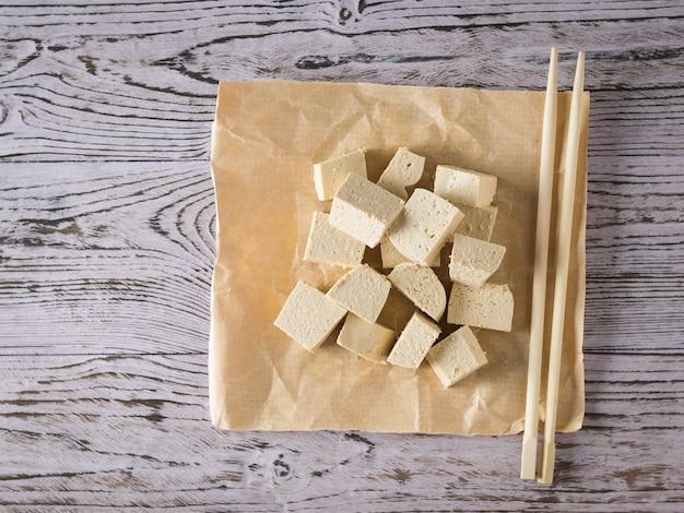 Деревянные палочки с кусочками тофу на деревянном столе. соевый сыр. вегетарианский продукт. плоская планировка.
