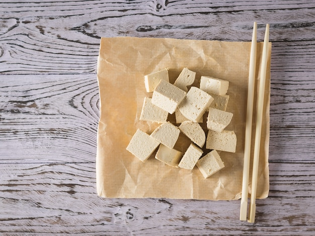 Wooden sticks with pieces of tofu on a wooden table. soy cheese. vegetarian product. flat lay.