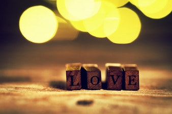 Wooden sticks with the word  love  and bokeh effect behind