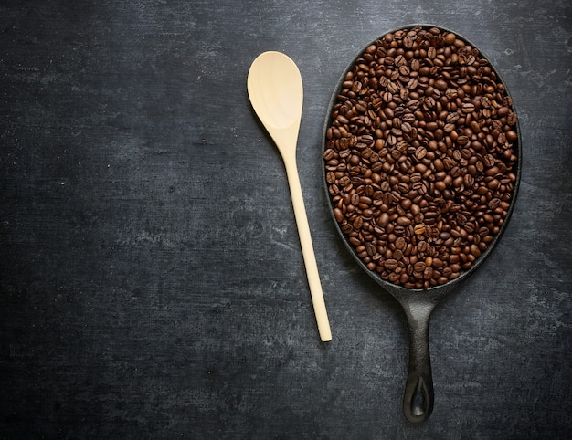 Wooden stirring spoon and frying pan with roasted coffee beans