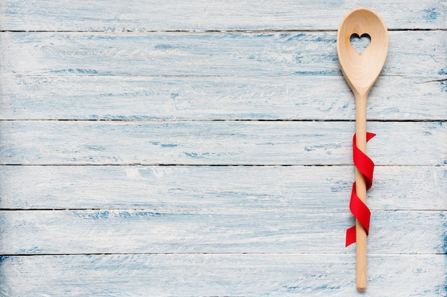 Wooden stirring spoon on light blue wood