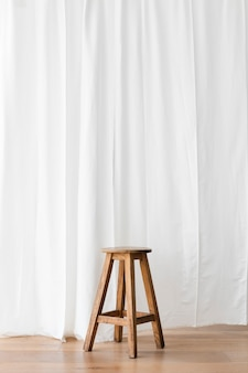Wooden stool in front of a white curtain