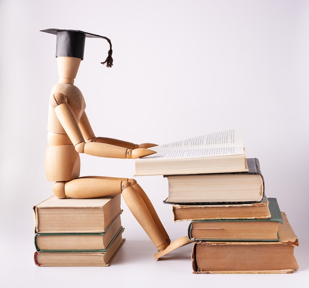 Деревянный студент сидит на стопке книг