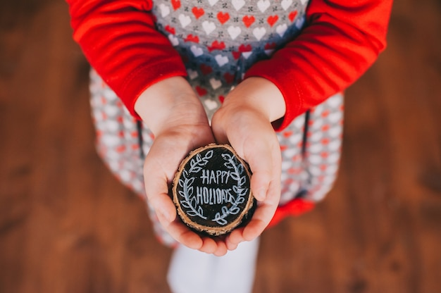 Wooden stump in children's hands with the words, happy holidays