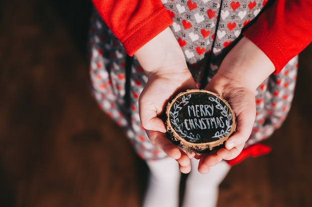 Wooden stump in children's hands with the words, merry christmas