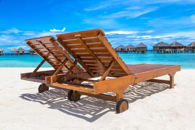 Деревянный шезлонг на тропическом пляже на мальдивах