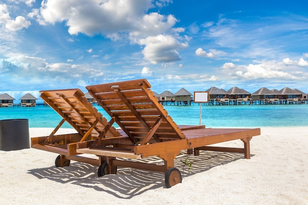 Wooden sunbed on tropical beach in the maldives