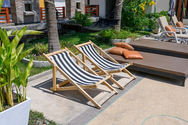 Wooden sunbeds with mattress on side of swimming pool