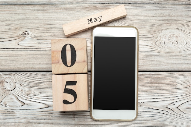 Wooden surface cube shape calendar fo 5 may on wooden surface