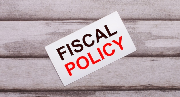 On a wooden surface, there is a white card with red text fiscal policy