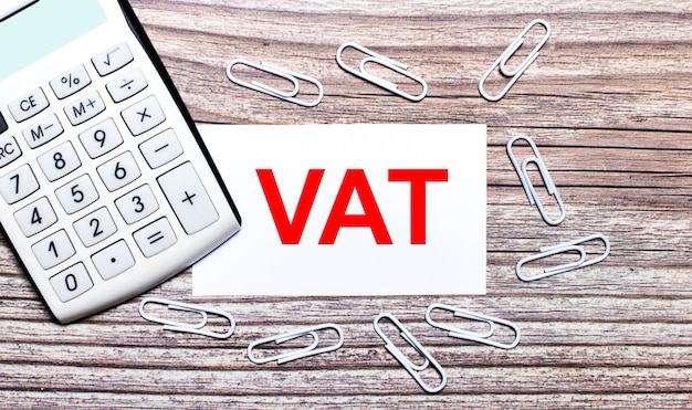 On a wooden surface, a white calculator, white paper clips and a white card with the text vat