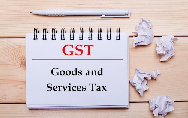 On a wooden surface, a white notebook with the inscription gst goods and services tax, a white pen and crumpled white pieces of paper