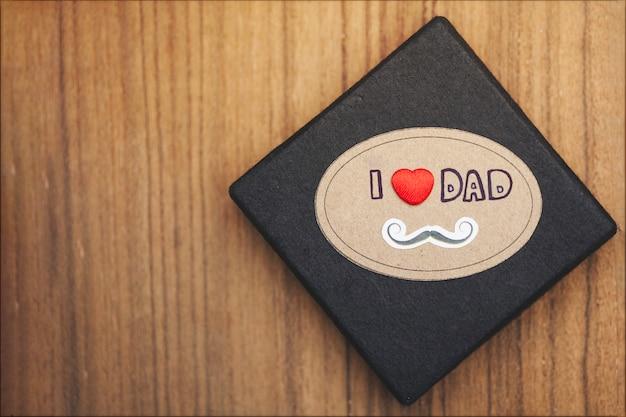 Superficie in legno con scatola nera per il giorno del padre