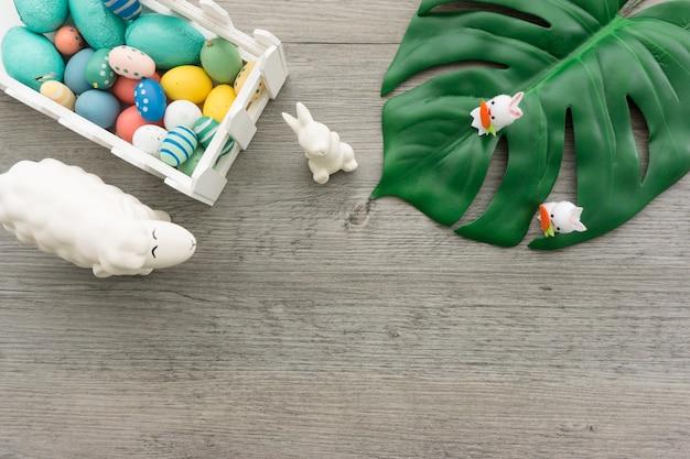 부활절 토끼, 녹색 잎 및 색 계란 나무 표면