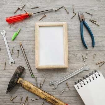 Wooden surface with frame, notebook and tools